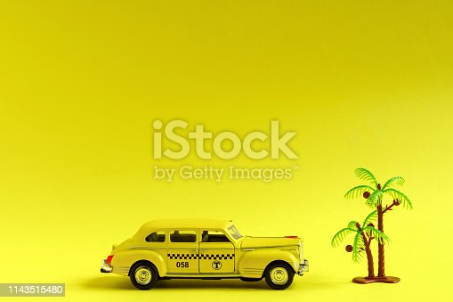 1087080996 istock photo Old retro yellow toy car taxi and toy palm on yellow background with copy space. Travel concept 1143515480