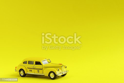 1087080996 istock photo Old retro yellow toy car taxi on yellow background with copy space. Travel concept 1144593359