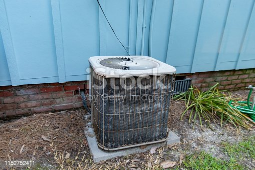 istock Old reusted air conditioner compresor sitting next to blue house 1152752411