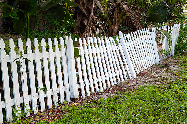 Old rickety fence in need of painting, fixing or replacing. stock photo