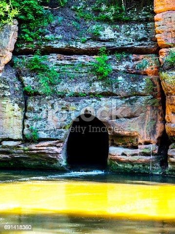 Old rock canal of river Ploucnice in sandstone wall near Straz pod Ralskem in Czech republic.