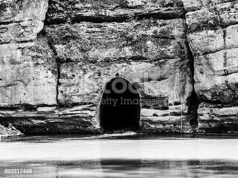 Old rock canal of river Ploucnice in sandstone wall near Straz pod Ralskem in Czech republic. Black and white image.