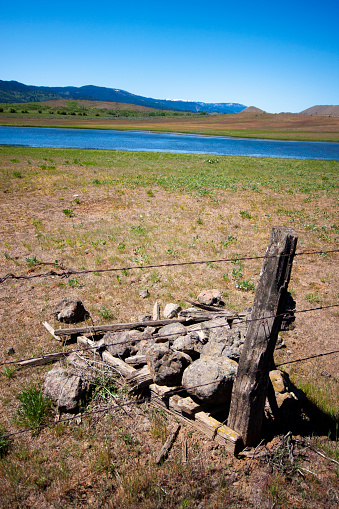 A rock-jack that is falling apart in West-Central Idaho near Council, with a pond and the Seven Devils Mountains in the background.