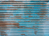 Peeled paint of rolling steel door in blue color. Blue shutter background. Retro style.