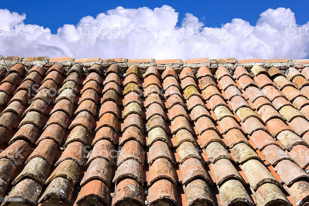 Old roof tiles, blue sky and clouds in the background stock photo