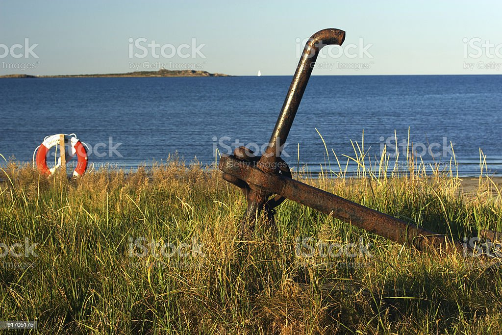 Old rosty iron anchor on the shore stock photo