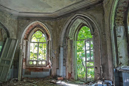 Old room with rotten window and doorway of an abandoned castle of Khvostov in gothic style, Lipetsk region