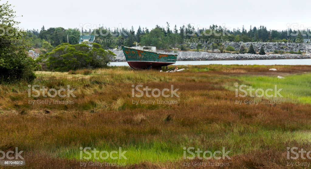 Old rotting fishing boat in background stock photo