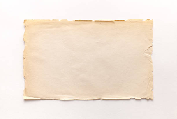 Old rough recycled paper with ragged edges on a white background with a shadow. A sheet of old rough recycled paper with splashes and ragged edges on a white background with a shadow. Copyspace for treasure map design. obsolete stock pictures, royalty-free photos & images