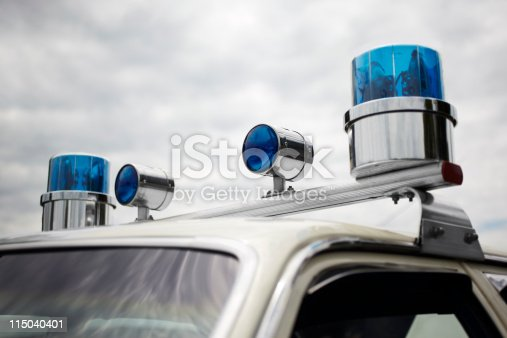 High resolution stock photo of older 1960's and 1970's style round blue police siren lights on a squad car.