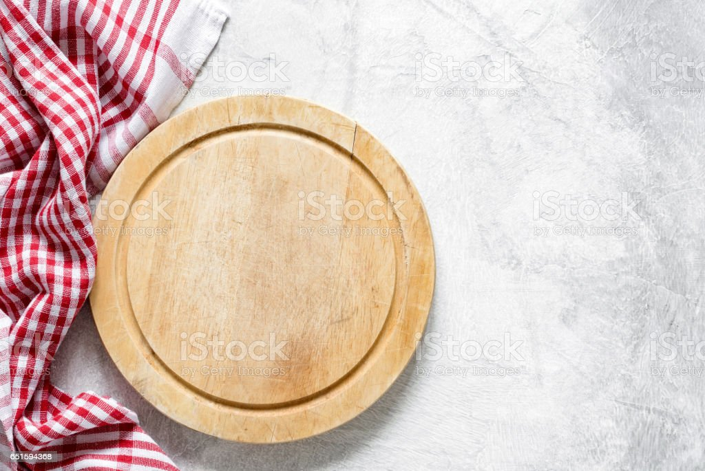Old round wooden cutting board or pizza board and red checkered  textile stock photo