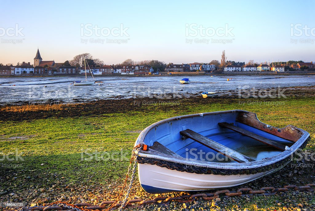 Old rowing boat in low tide harbour landscape at sunset royalty-free stock photo