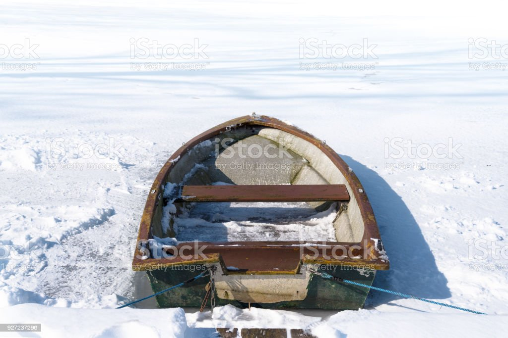 Old rowing boat in the frozen lake on a sunny winter day, concept metaphor for burn out, slow down and standstill in the business career or in private life, copy space stock photo