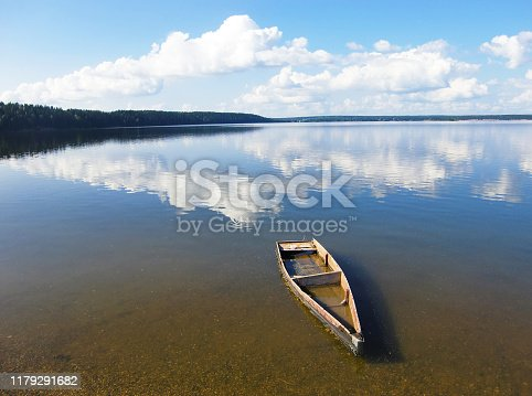 Old rowing boat under water at the shore. The clouds are beautifully reflected in the water. Forsaken broken little craft in a river. Abandoned old wooden fishing boat near pier in summer in river.