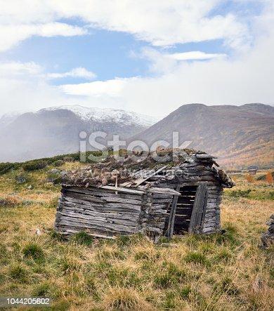 Broken log cabin exterior in a mountain area in autumn.