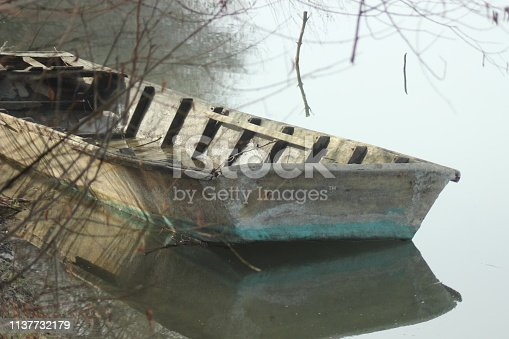 View on an Old ruined boat sinking half in river water