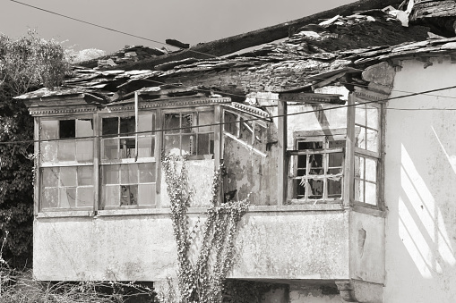 Old ruined residential building ,galería and broken roof and glasses.