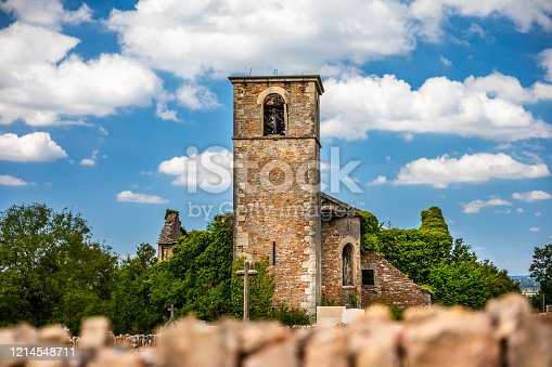 Old ruins of an abandoned stone church steeple, bell tower next to a beautiful cemetery. This color photography was taken during a sunny summer day, in end of july, in Isere department in middle of meadows between the villages of Bourcieu and Leyrieu in Auvergne-Rhone-Alpes region in France, Europe.