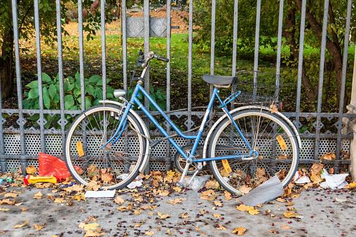old rundown bike locked to a park gate in Munich, Germany
