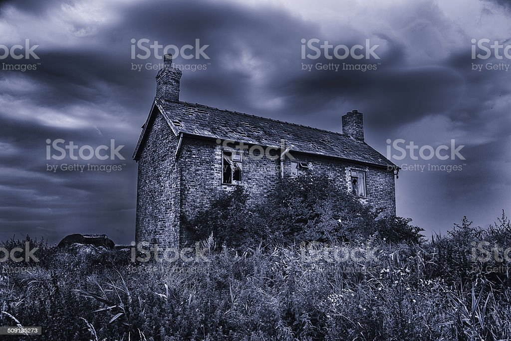 Old run-down spooky haunted house with stormy skies stock photo