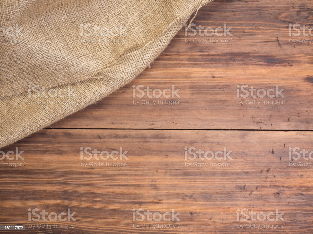 Old rural wooden table boards and burlap vintage background, photo top view. Hessian, sacking texture on wooden background for your design stock photo