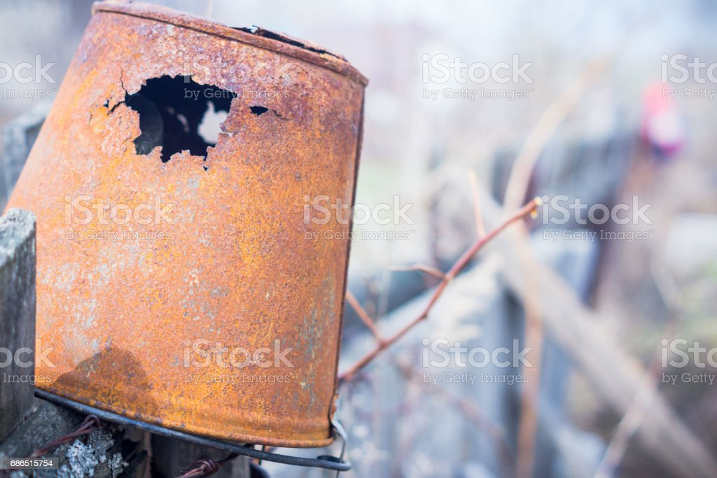 Old rusted bucket on the wooden fence royalty free stockfoto