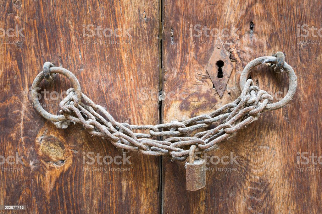 Old rusted padlock, rusted chain, and keyhole on a closed wooden aged grunge door stock photo