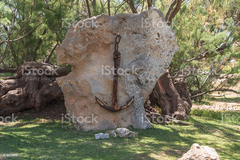 Old rusted ship's anchor on a stone. stock photo