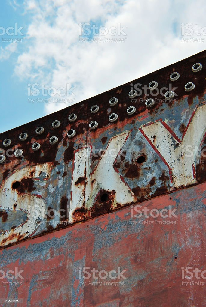Old Rusted Sign Word Sky Against Clouds royalty-free stock photo