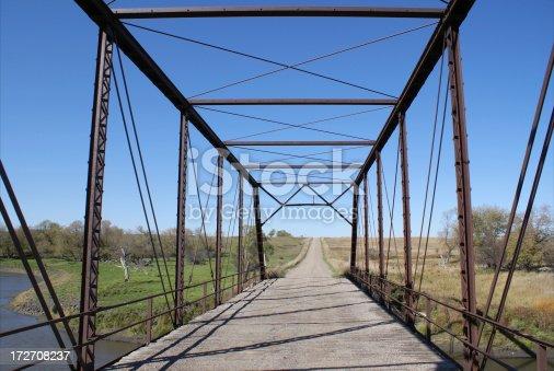 old rusted steel girder bridge over river
