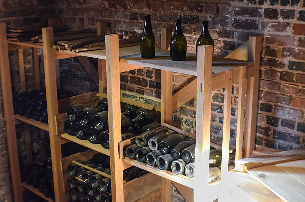 old rustic bottles of wine in cellar shelves - mini weinflaschen stock-fotos und bilder