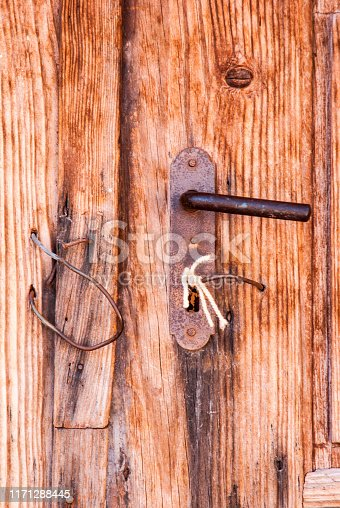 Old rustic door open with rusty lock, key and keyhole