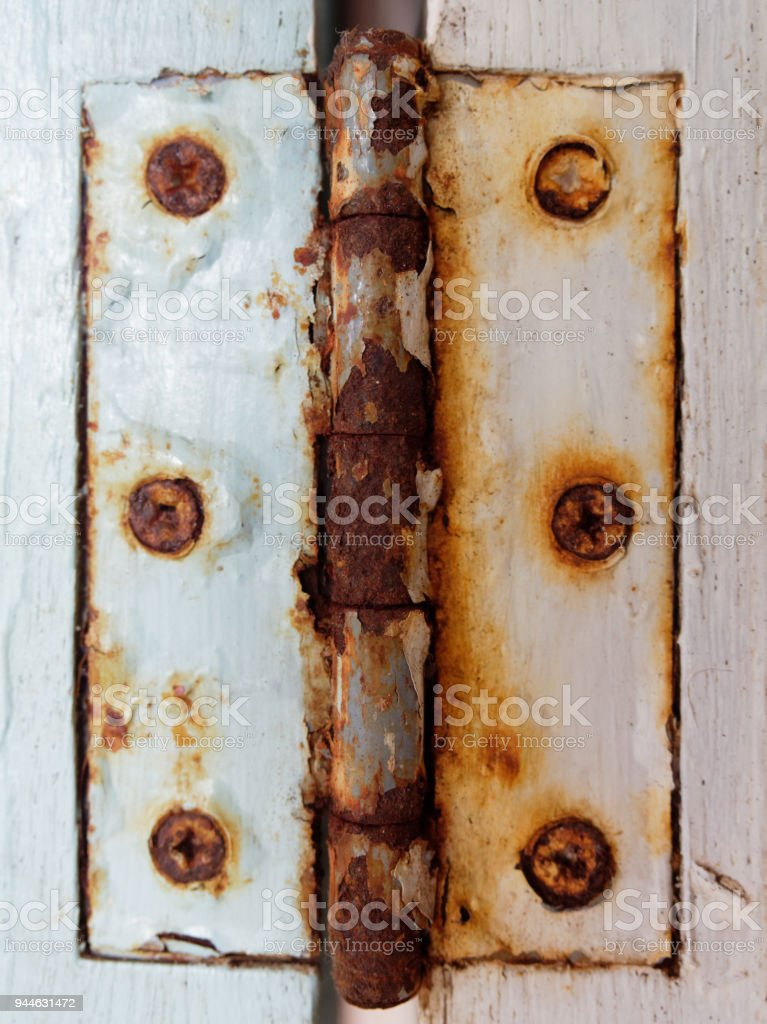Old rustic metal hinge with screw over white wooden window in grunge, retro, and vintage style stock photo
