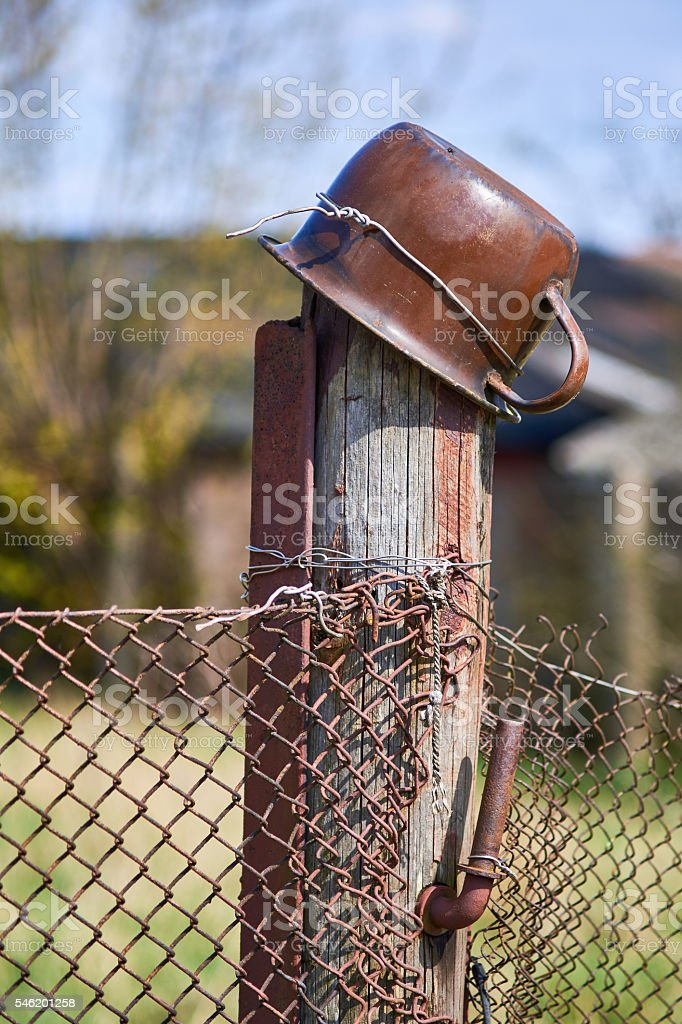 Old rustic pole with a metal pot on it stock photo