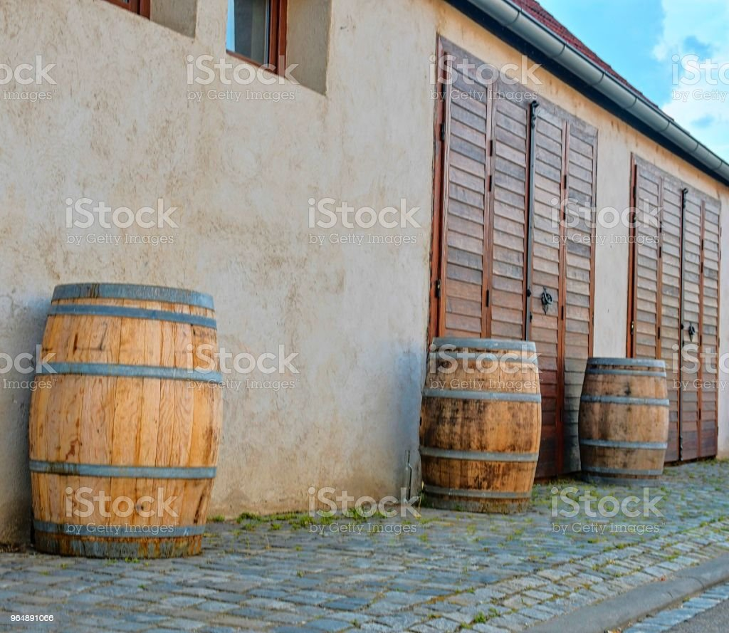 Old rustic wine barrels in front of modern wine cellar. Wine background in Europe. Czech Republic, South Moravia royalty-free stock photo