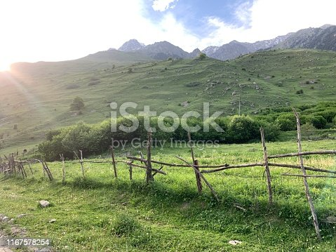 Old rustic wooden fence in the mountains village, stretching into the distance.