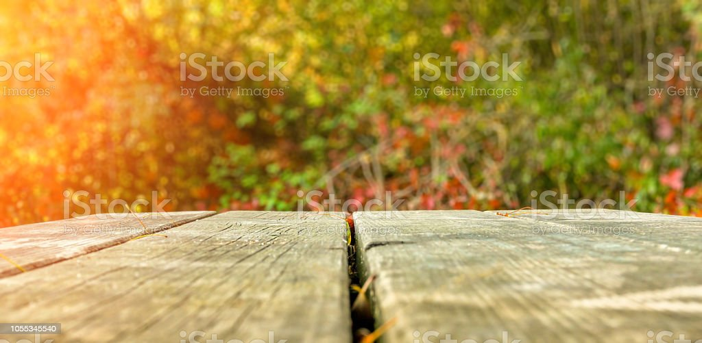 Old rustic wooden park table against autumnal scene stock photo