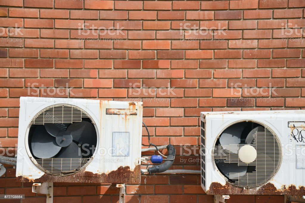 Old rusting metal exterior fitted air conditioning unit mounted on wall needing maintenance stock photo