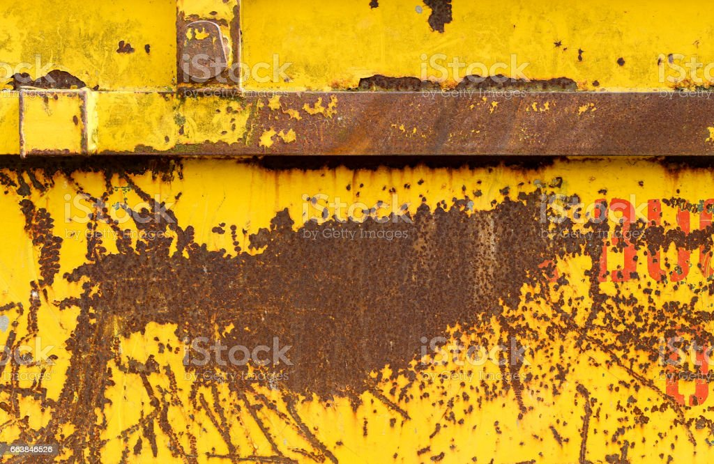 Old rusting metal skip container with yellow pealing paint stock photo