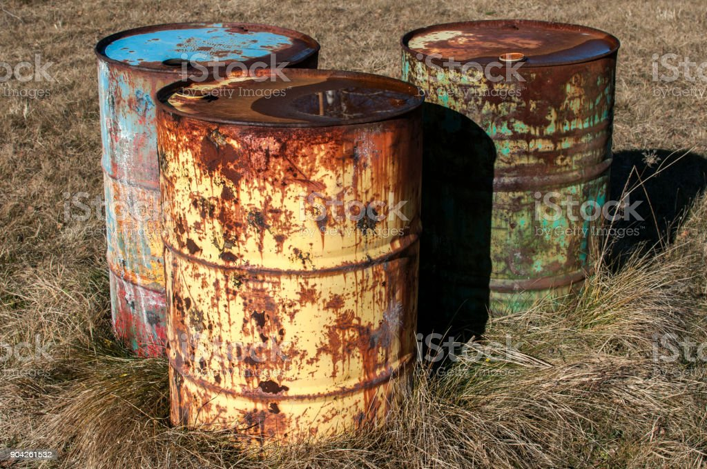 Old rusty abandoned fuel barrel drums stock photo