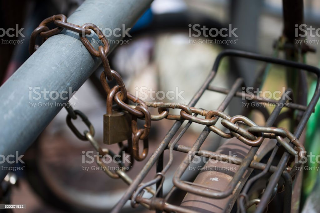 Old rusty anchor iron chain locked the bicycle stock photo