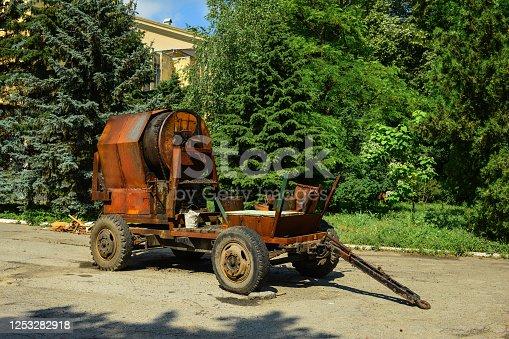 old rusty asphalt repair machinebarrels with bitumen for road construction.