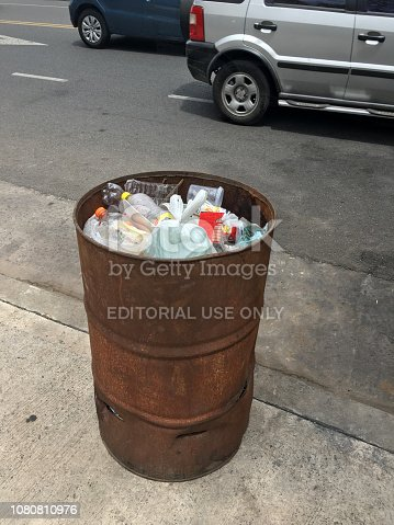 Buenos Aires, Argentina - December 9, 2018: Improvised garbage bin full of plastics made out from old rusty barrel. People are doing their best effort to keep the city clean
