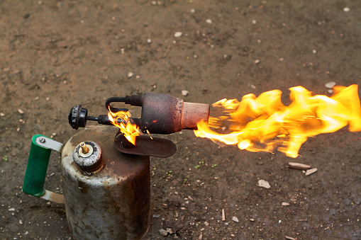 istock Old rusty blowtorch with fire. 1257550754