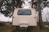 Old rusty camper parked in the woods. Low angle view.