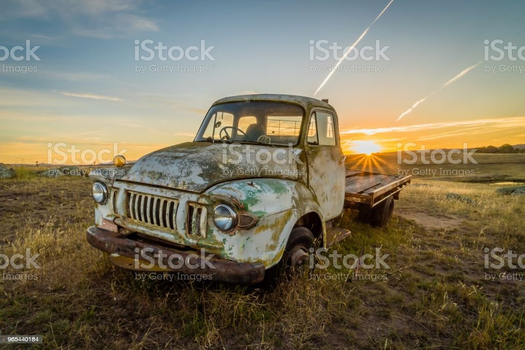 Old rusty car in a field in Australia with sunset in the background royalty-free stock photo
