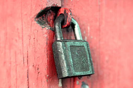 Old rusty cast iron padlock on red painted door