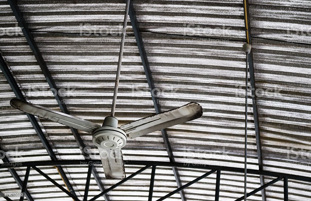 Old Rusty Ceiling Fan Hang On Warehouse Ceiling. Royalty Free Stock Photo