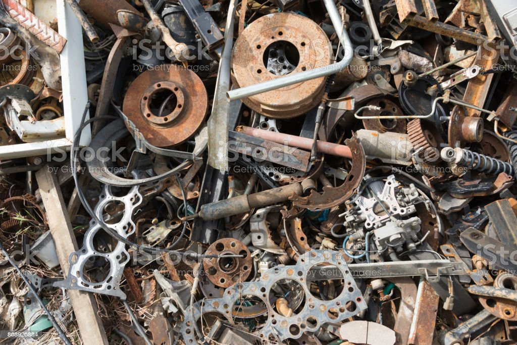 Old rusty corroded car parts in car scrapyard. Car recycling.Wrecking Machinery Parts wait for reused or to be a part for repair. stock photo
