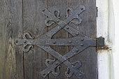 Old rusty door hinge on wooden vintage doors.